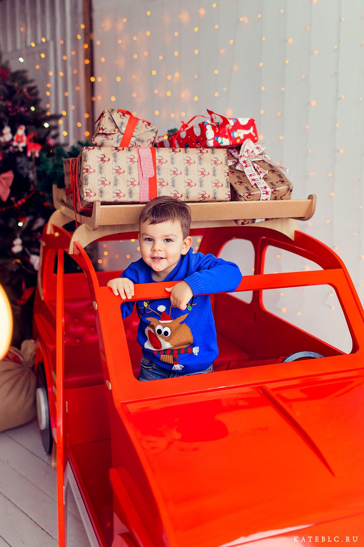 Новогодняя фотосессия для мальчика в студии с красной машиной. Детский фотограф в Москве Катя Белоцерковская. kateblc.ru