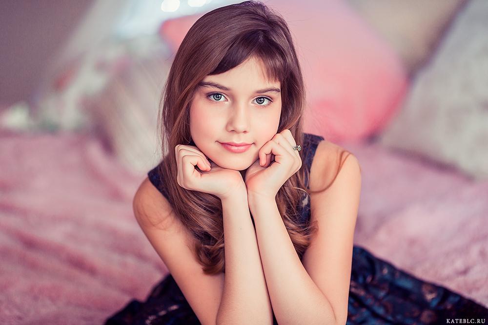 Яркие фотосессии для девочек в студии. Портрет девочки, сидящей на кровати.