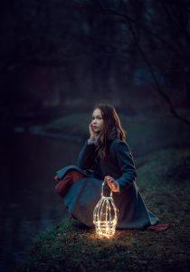 девочка сидит на берегу с фонарем
