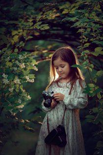 Девочка с фотоаппаратом в цветущих кустах жасмина