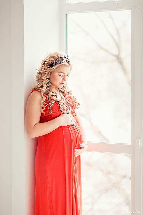 Беременная девушка в ярком красном платье у окна. Фотосессия в студии. Фотограф в Москве Катрин Белоцерковская
