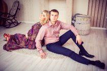 Беременная девушка с мужем сидят спинами друг к другу на полу возле камина