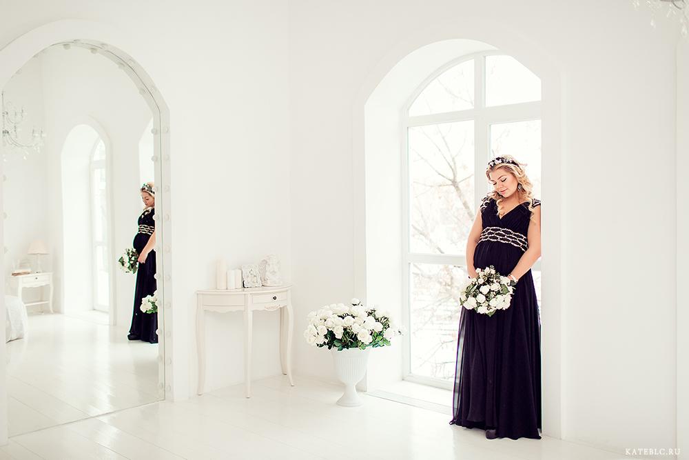 Беременная девушка в черном платье у окна в студии. Яркая фотосессия беременности в Москве