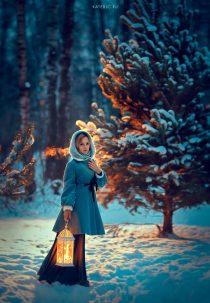 девушка в зимнем заснеженном лесу с фонарем