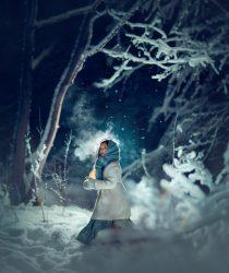 Девочка с фонариком в зимнем заснеженном лесу. Волшебная фотография