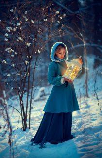 Девушка с фонарем на природе зимой